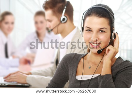 Smiling young woman in headset with business people on background