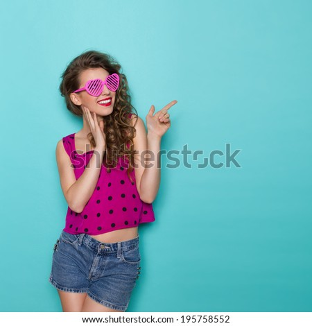 Smiling young woman in heart shaped glasses pointing at copy space. Three quarter length studio shot on teal background. - stock photo