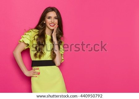 Smiling young woman in lime green dress posing with hand on chin and looking at camera. Three quarter length studio shot on pink background. - stock photo