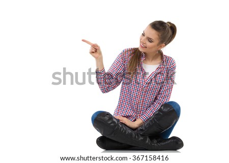 Smiling young woman in lumberjack shirt, jeans and black boots sitting on a floor with legs crossed, pointing and looking away. Full length studio shot isolated on white. - stock photo