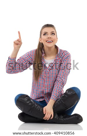 Smiling young woman in lumberjack shirt, jeans and black boots sitting on a floor with legs crossed pointing and looking up. Full length studio shot isolated on white. - stock photo