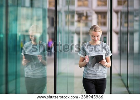 Smiling young woman in modern glass office interior using tablet  - stock photo