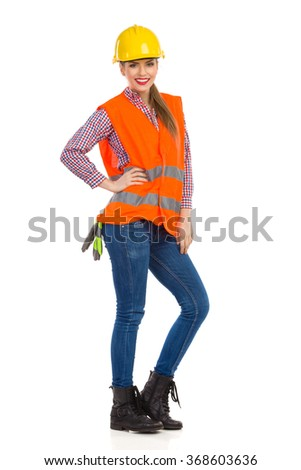 Smiling young woman in orange reflective vest, lumberjack shirt, jeans and black boots, posing in yellow hardhat and holding hand on hip. Full length studio shot isolated on white. - stock photo