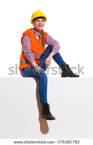 Smiling young woman in orange reflective vest, yellow hardhat, lumberjack shirt, jeans, black boots, sitting on top in the sunlight. Full length studio shot isolated on white. - stock photo