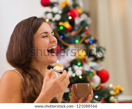 Smiling young woman in pajamas eating cookies with hot chocolate near Christmas tree - stock photo