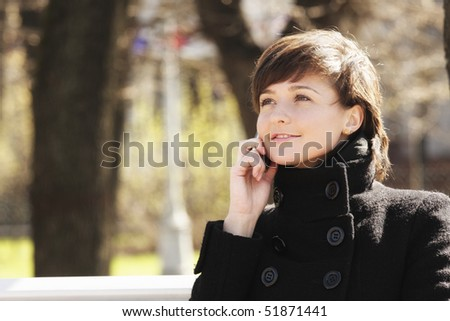 Smiling young woman in springtime park with cellphone