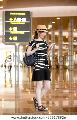 Smiling young woman in straw hat waiting for flight, standing in public Wi-Fi area in modern airport terminal, holding mobile phone, looking at screen, using smartphone app, messaging, full length - stock photo