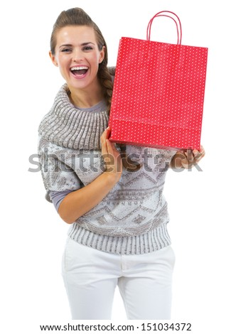 Smiling young woman in sweater showing christmas shopping bag
