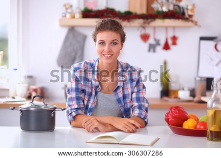 Smiling young woman in the kitchen, isolated on christmas background - stock photo