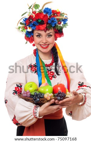 Smiling young woman in the Ukrainian national clothes with fruit - stock photo