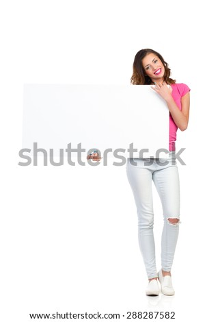 Smiling young woman in torn jeans and pink shirt standing and holding white placard. Full length studio shot isolated on white