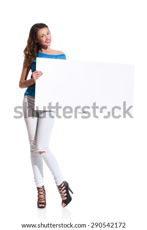 Smiling young woman in torn jeans and pink shirt standing and holding white placard. Full length studio shot isolated on white - stock photo
