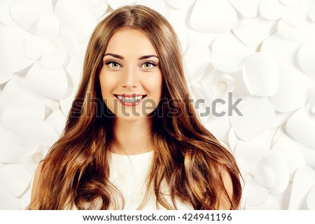 Smiling young woman in white dress posing by the background of white paper flowers. Beauty, fashion. Healthy teeth. Cosmetics. - stock photo