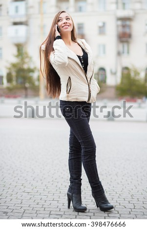 Smiling young woman in white jacket and black jeans posing with mobile phone outdoors