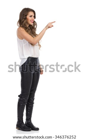 Smiling young woman in white shirt, black leather trousers and boots standing, pointing and looking away. Full length studio shot isolated on white. - stock photo