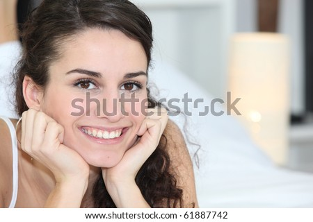 Smiling young woman laid in a bed