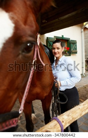 Smiling young woman leaning towards horse. - stock photo
