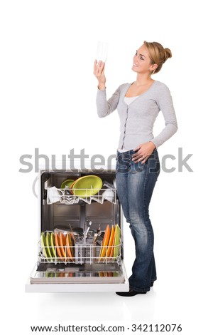 Smiling young woman looking at clean glass while standing by dishwasher over white background - stock photo