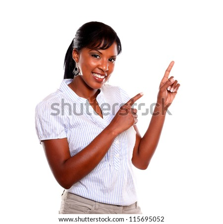 Smiling young woman looking at you and pointing up against white background - stock photo