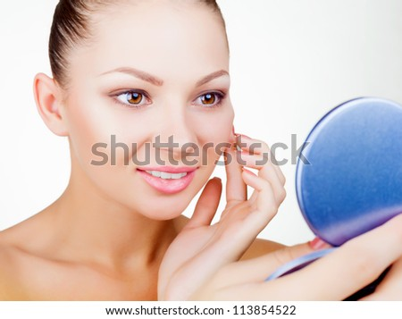 Smiling young woman looking in the mirror isolated on white background - stock photo