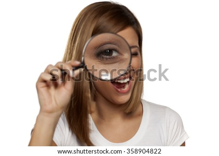 smiling young woman looking through a magnifying glass - stock photo