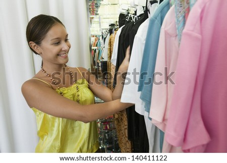 Smiling young woman looking through clothing rack in the store - stock photo