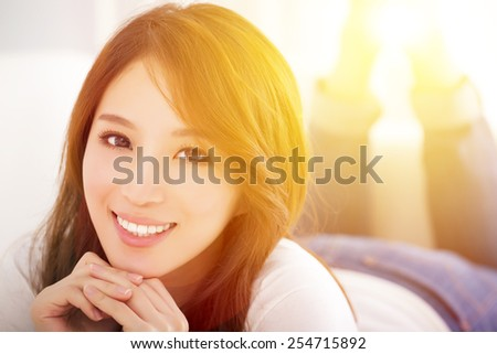 smiling Young woman  lying on the sofa with sunlight background - stock photo