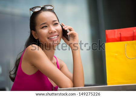 Smiling young woman making a call to take a break from shopping - stock photo