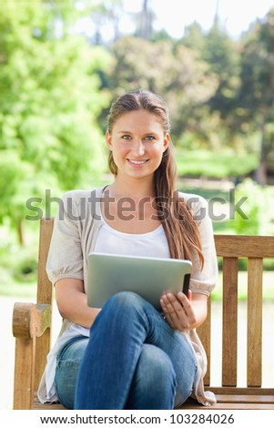 Smiling young woman on a park bench with a tablet computer