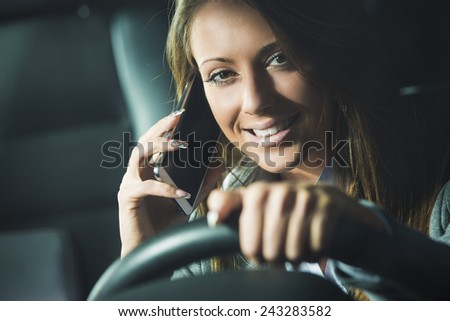 Smiling young woman on the phone driving late at night. - stock photo