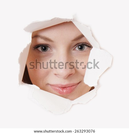 smiling young woman peeking through hole in paper wall  - stock photo