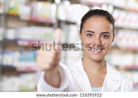 Smiling young woman pharmacist giving thumbs up - stock photo