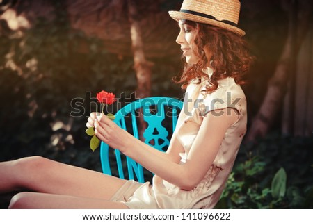 smiling young woman play with flower, sitting in garden summer day - stock photo