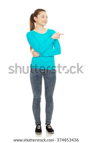 Smiling young woman pointing aside. - stock photo