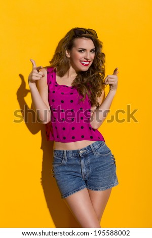 Smiling young woman pointing at camera. Three quarter length studio shot on yellow background. - stock photo