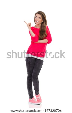 Smiling young woman pointing up at empty space. Full length studio shot isolated on white. - stock photo