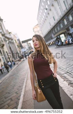 Smiling young woman portrait outdoors in Milan. Lifestyle concept of youth, fun, enjoy life.