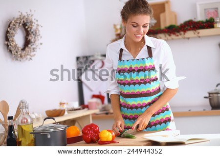 Smiling young woman preparing salad in the kitchen - stock photo