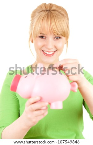 smiling young woman putting euro coin into pink piggy bank, white background