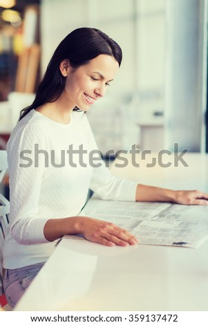 smiling young woman reading newspaper at cafe - stock photo
