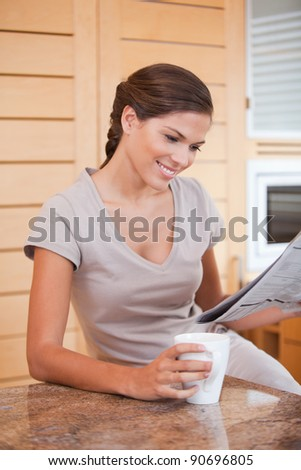 Smiling young woman reading newspaper in the kitchen
