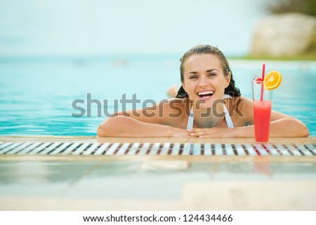Smiling young woman relaxing in pool with cocktail - stock photo
