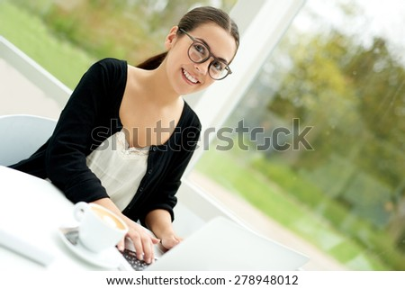 Smiling young woman relaxing with her laptop computer at home sitting at a table on her outdoor patio wearing sunglasses with a cup of fresh hot coffee alongside - stock photo