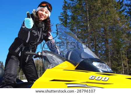 Smiling young woman riding a snowmobile - stock photo