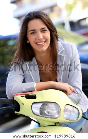 Smiling young woman riding scooter in town - stock photo