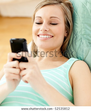 Smiling young woman sending a text lying on a sofa at home - stock photo