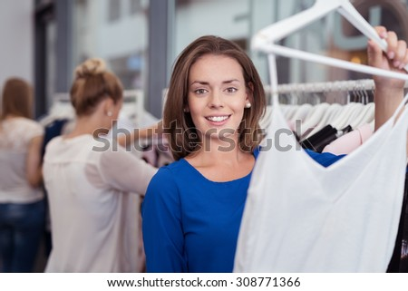 Smiling young woman shopping for fashion garments in a boutique store holding up a filmy white summer top with a smile - stock photo