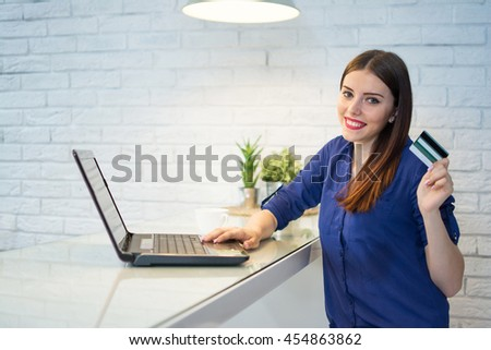 Smiling young woman shopping online with credit card and laptop.