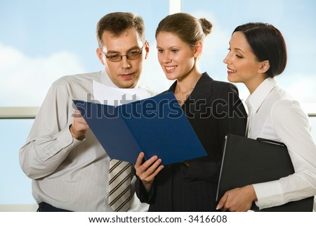 Smiling young woman showing documents to her boss and curious girl looking into the paper case - stock photo