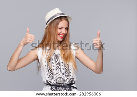 Smiling young woman showing thumbs up, isolated on gray background. Happy girl joyfully winking - stock photo